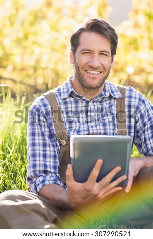 Portrait of a smiling farmer using a digital tablet on the grass