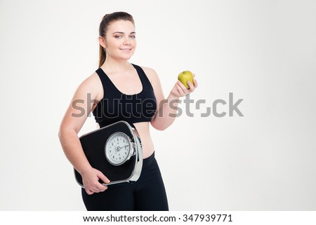 Portrait of a smiling fat woman holding weighing machine and apple isolated on a white background - stock photo