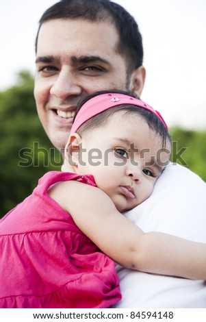 Portrait of a smiling father holding the baby girl in his arms with love and affection - stock photo