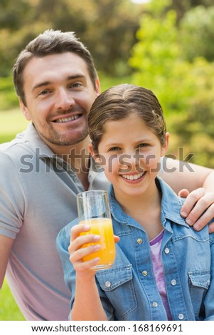 Portrait of a smiling father with young daughter holding orange juice in the park