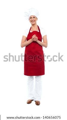 Portrait of a smiling female chef, hands clasped