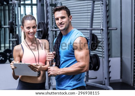Portrait of a smiling female coach writing on a clipboard - stock photo