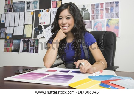 Portrait of a smiling female fashion designer working at desk - stock photo