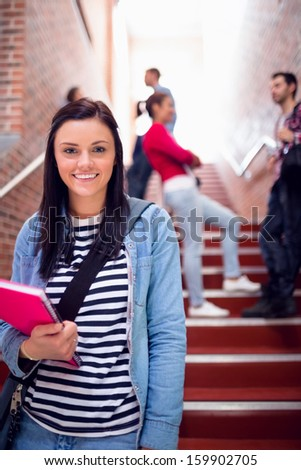 Portrait of a smiling female holding books with students behind on stairs in the college - stock photo