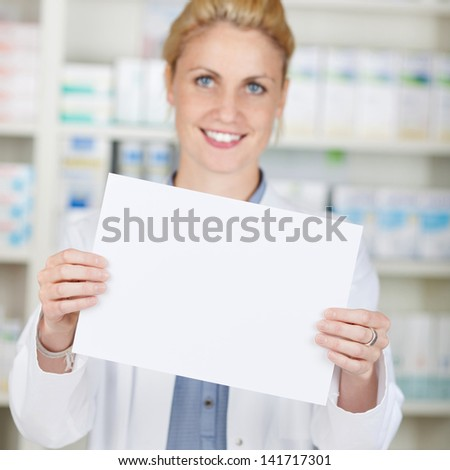 Portrait of a smiling female pharmacist holding blank paper at drugstore - stock photo