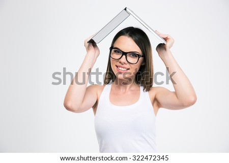 Portrait of a smiling female student holding laptop computer over head isolated on aw hite background - stock photo