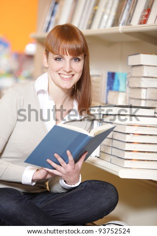portrait of a smiling female student in a library - stock photo