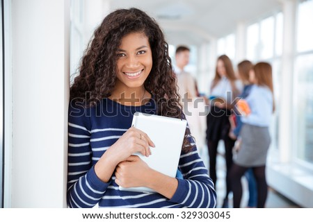 Portrait of a smiling female student standing in university hall with classmates on a background - stock photo
