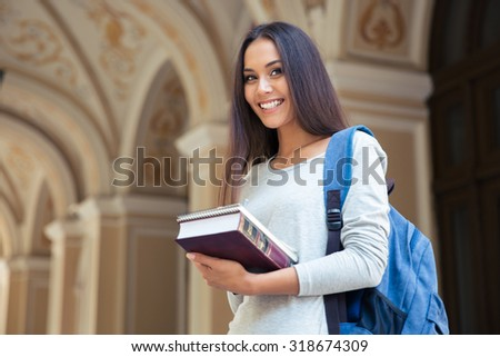 Portrait of a smiling female student standing outdoors and looking at camera - stock photo