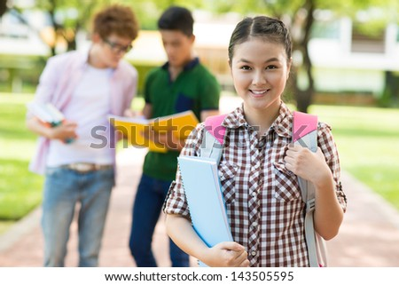 Portrait of a smiling female student standing outside on the foreground - stock photo