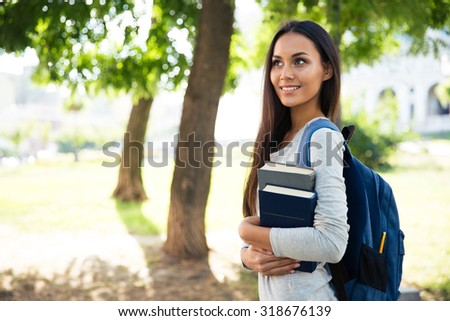 Portrait of a smiling female student walking outdoors - stock photo