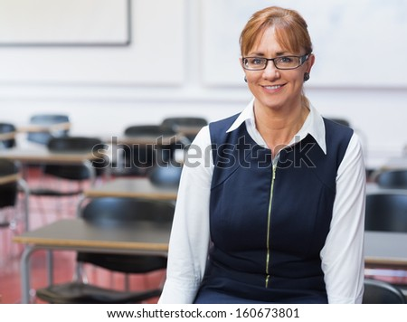 Portrait of a smiling female teacher in the class room - stock photo