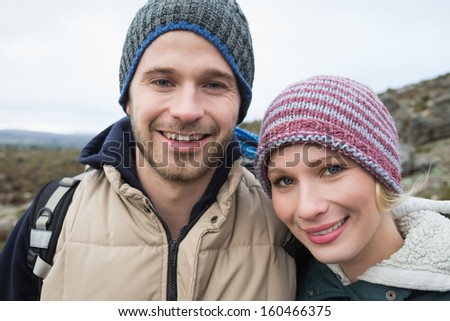 Portrait of a smiling fit couple on a hike in the countryside against clear sky - stock photo
