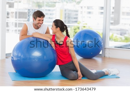 Portrait of a smiling fit young couple with exercise ball sitting at a bright gym - stock photo
