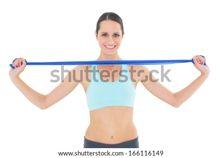 Portrait of a smiling fit young woman holding blue yoga belt over white background