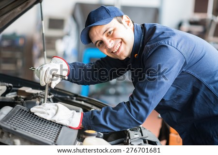 Portrait of a smiling fixing a car engine in his garage - stock photo