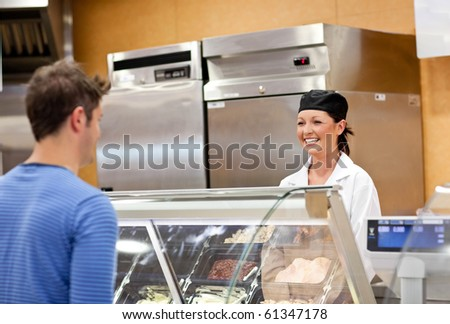 Portrait of a smiling food retailer with a male customer in her shop - stock photo