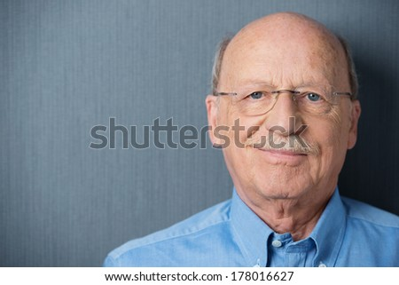 Portrait of a smiling friendly senior man with a moustache wearing glasses on a grey background with copyspace