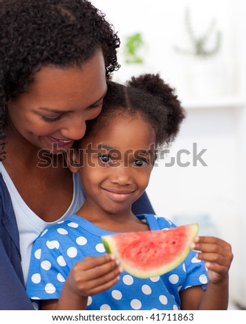 Portrait of a smiling girl eating fruit with her mother - stock photo