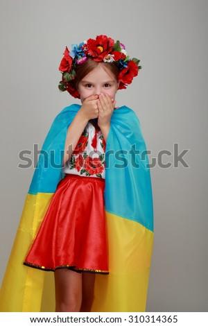 Portrait of a smiling girl in Ukrainian national headdress holding a Ukrainian flag on a gray background - stock photo