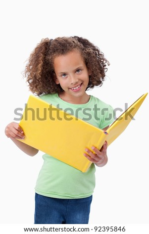 Portrait of a smiling girl reading a fairy tale against a white background - stock photo