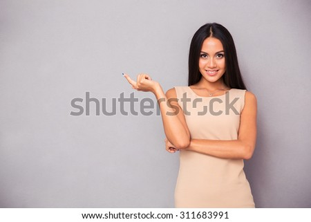 Portrait of a smiling girl showing finger away over gray background - stock photo