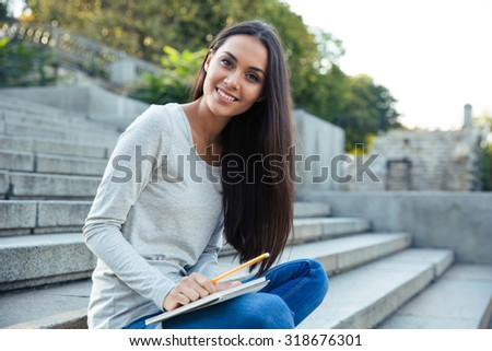 Portrait of a smiling girl sitting on the city stairs with pencil and notepad outdoors and looking at cmaera - stock photo