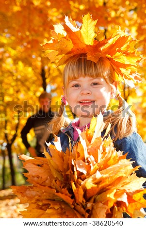 Portrait of a smiling girl with autumn leaves - stock photo