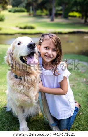Portrait of a smiling girl with her pet dog in the park - stock photo