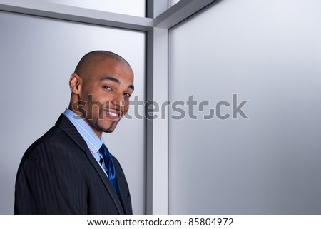 Portrait of a smiling good-looking businessman beside an office window. - stock photo