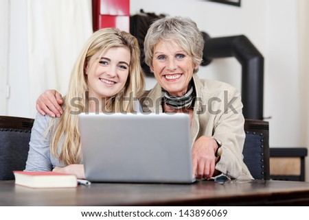 Portrait of a smiling grandmother and granddaughter using laptop at home - stock photo