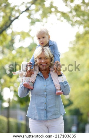 Portrait of a smiling grandmother piggyback ride with baby - stock photo