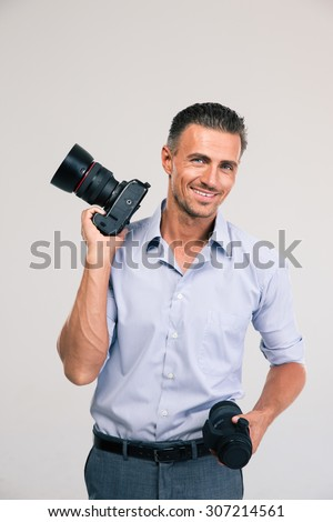 POrtrait of a smiling handsome photographer holding camera and looking at camera - stock photo