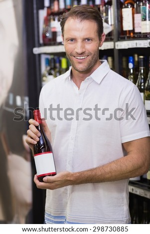 Portrait of a smiling handsome showing a wine bottle in supermarket - stock photo