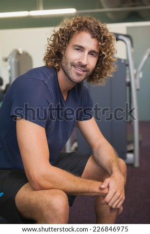 Portrait of a smiling handsome trainer sitting in the gym - stock photo