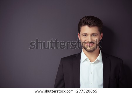 Portrait of a Smiling Handsome Young Businessman Smiling at the Camera Against Gray Wall with Copy Space on the Left Side. - stock photo