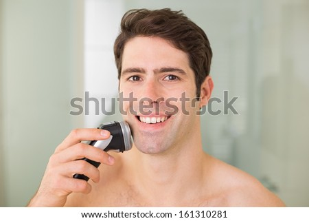 Portrait of a smiling handsome young shirtless man shaving with electric razor - stock photo
