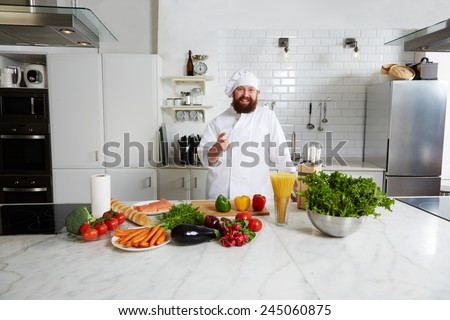 Portrait of a smiling happy chef pointing with finger to you standing on big kitchen - stock photo