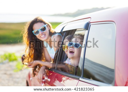 Portrait of a smiling happy mother with two children at beach in the car. Holiday and travel concept