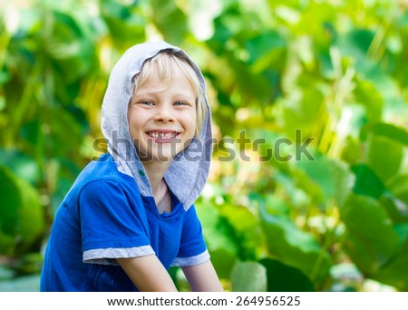 Portrait of a smiling, healthy child out in nature next to a Lilly pond - stock photo