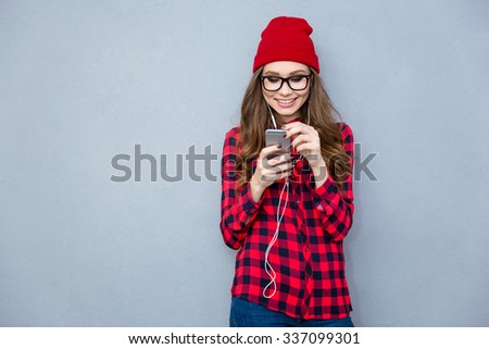 Portrait of a smiling hipster woman using smartphone with headphones on gray background