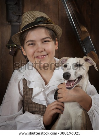 Portrait of a smiling hunter boy with Whippet dog indoors