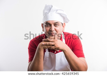 Portrait of a smiling indian male chef resting chin on both hands, leaning forward, asian male chef, isolated over white background - stock photo