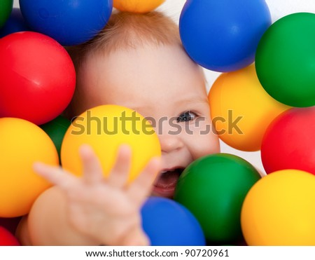 Portrait of a smiling infant lying among colorful balls - stock photo
