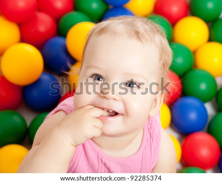 Portrait of a smiling infant sitting among colorful balls - stock photo