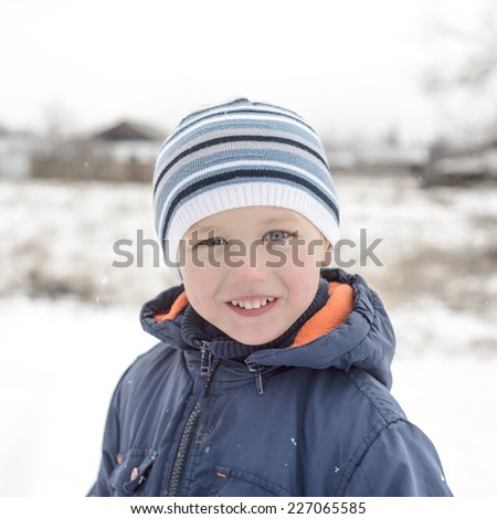 portrait of a smiling little boy in winter - stock photo