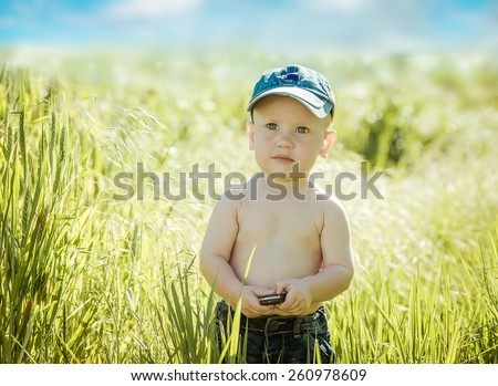 portrait of a smiling little boy on a green grass, - stock photo