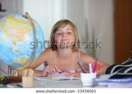 Portrait of a smiling little girl doing homework - stock photo