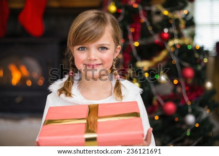 Portrait of a smiling little girl holding a wrapped gift at home in the living room - stock photo