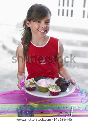 Portrait of a smiling little girl holding tray of cupcakes - stock photo